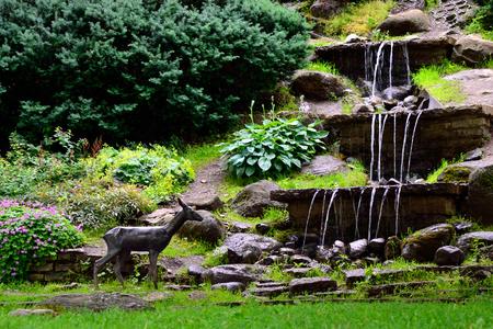 Waterfalls in public garden and statue of roe. Tallinn, Estonia.