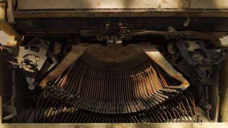 Detail of an old typewriter set on the floor. Retro machine technology. focus selection.