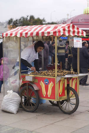 ISTANBUL,JANUARY 30,2011:Street peddler grid and selling chestnut in a small barrow at Eminonu region
