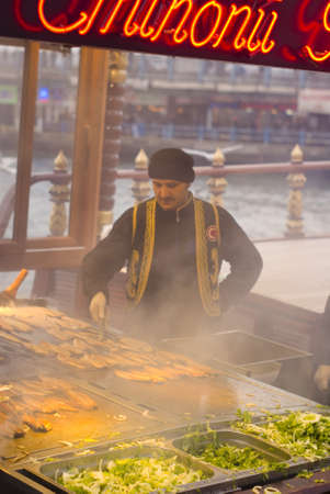 ISTANBUL,JANUARY 30,2011:cook grid fish in a boat at eminonu region Editorial
