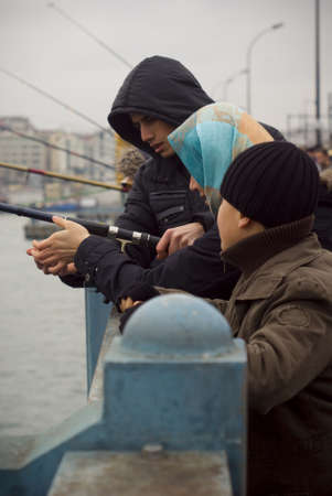 ISTANBUL,TURKEY,JANUARY 30,2011- Family fishing on the galata bridge at eminonu region