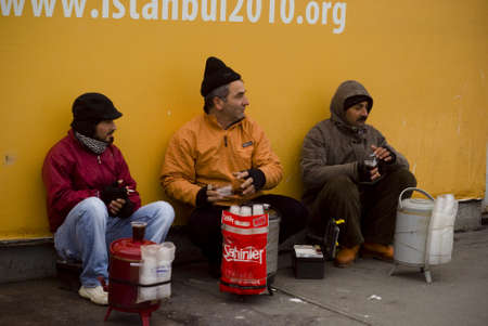 ISTANBUL,TURKEY,JANUARY 30,2011: Tea sellers sitting and waiting on the galata bridge at eminonu region Editorial