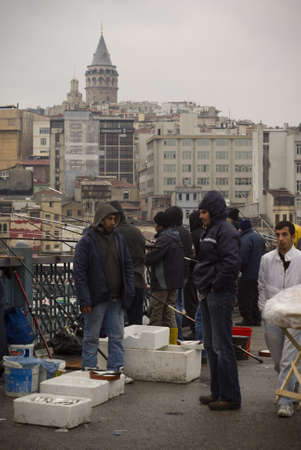 ISTANBUL,TURKEY,JANUARY 30,2011- Fishermans fishing on the galata bridge at eminonu region Editorial