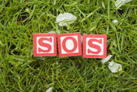 SOS letter blocks on the grass Stock Photo