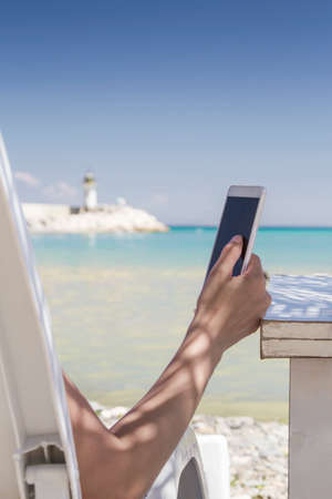 Woman using her smartphone at the beach Stock Photo