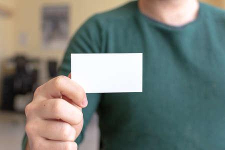Mock-up di biglietto da visita - uomo che tiene una carta in bianco per i clienti. Modello di biglietto da visita.