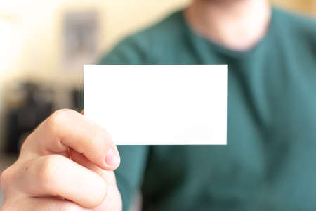 Business Card Mock-Up - Man Holding a Blank Card for Clients. Business Card Template. 版權商用圖片