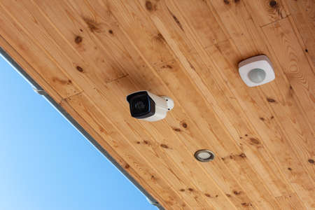 Modern Outdoor CCTV Camera on a Ceiling. Concept of Surveillance and Monitoring. Surveillance camera Anti-theft System Concept.