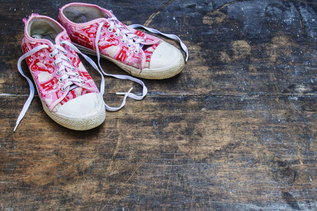 Pink and White Shoes With Love Shape Strap. Old Pink Shoes. Worn Out Pink White Shoes Flat lay on Old Blackboard. Stock Photo