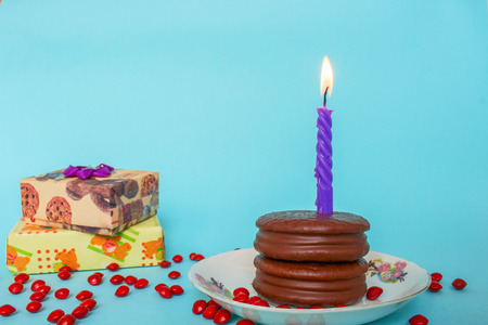 Chocolate Birthday Cake With Purple Candle and Red Chocolate Candy and Gift Box on Blue Background