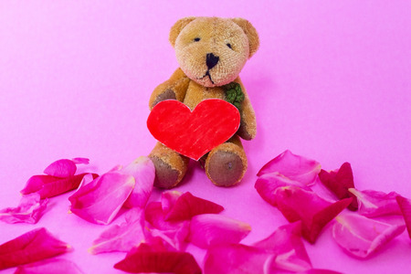 Love Made From Paper on Lap of Yellow Bear Doll. Bear Doll Lean Back on Pink Background. Doll Surrounding by Rose Petal