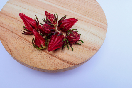 Top View of Rosella or hibiscus Seeds on Wood Round Cutting Board on White Background Stock Photo