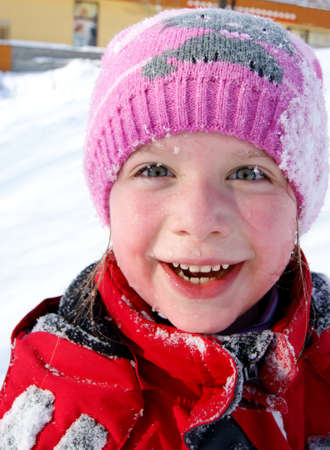 Happy little smiling girl outdoors in the snow in winter clothing