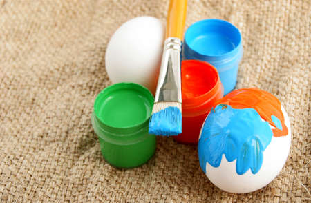 Easter eggs brush and Jars with a bright paint on a rough canvas background