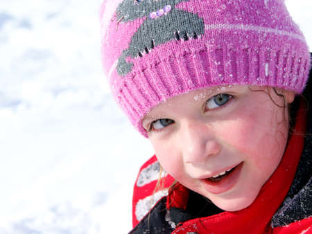 Little smiling girl outdoors in the snow in winter clothing Stock Photo