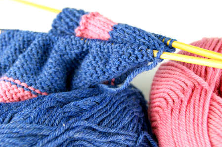 Knitting. Two balls two needles with a cloth on a white background Stock Photo