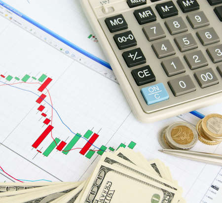 Calculator, pen, dollars and euro on the exchange chart background photo