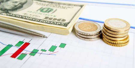 Dollar notes, euro coins and pen on the exchange chart background Stock Photo