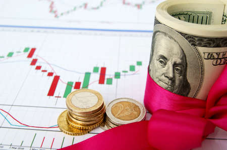 US dollars rolled up and tightened with pink band  and euro coins on the exchange chart background