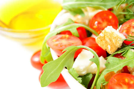 Mixed salad with cherry tomatoes, arugula, mozzarella and olive oil on white background