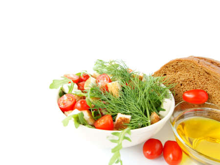 Mixed salad with cherry tomatoes, arugula, mozzarella, a loaf of rye bread and olive oil on white background Stock Photo