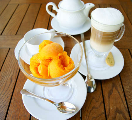 orange ice cream in a glass bowl and glass of coffee latte  on the background of the wooden table surface