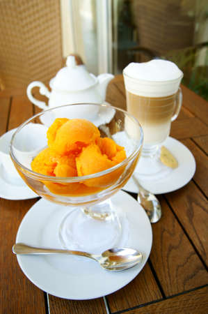 orange ice cream in a glass bowl and glass of coffee latte  on the background of the wooden table surface photo