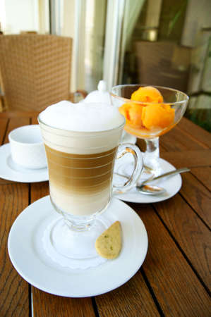 coffees: glass of coffee latte and orange ice cream in a glass bowl on the background of the wooden table surface