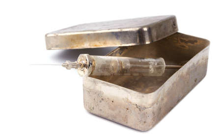 Dirty glass syringe in a rusty steel box on a white background Stock Photo