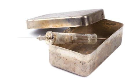 delincuencia: Jeringa de vidrio sucio en una caja de acero oxidado en un fondo blanco