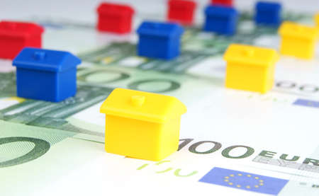 yellow, blue and red small houses on the background of euro banknotes Stock Photo