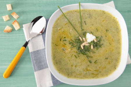 GREEN ZUCCHINI SOUP ON WOODEN TABLE