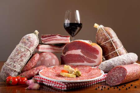 worsten: samenstelling van gemengde Italiaanse vleeswaren op houten tafel