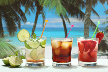 cola: alcoholic cocktails with rum strawberry and lime on the beach Stock Photo
