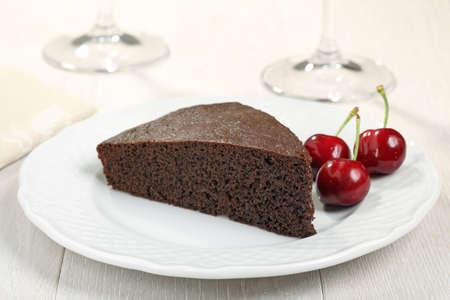 tort: chocolate cake with cream and cherry on white plate Stock Photo