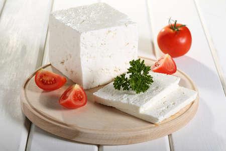 queso: queso feta tomate y especias en la tabla de cortar