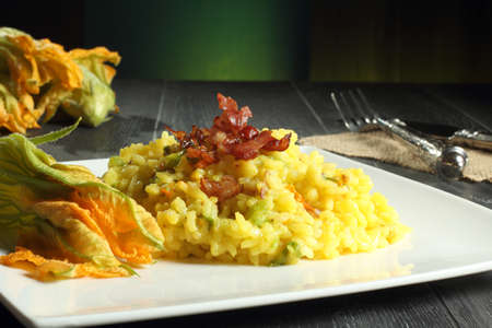 risotto with zucchini flower gray table green background