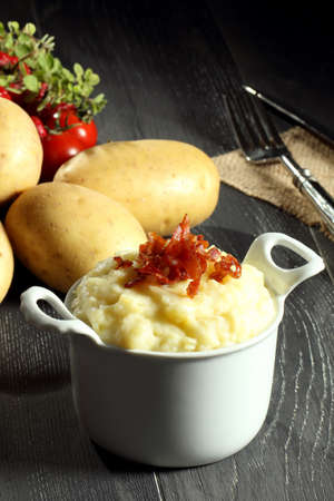 mashed potatoes with bacon white bowl gray background Foto de archivo
