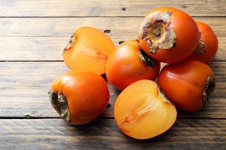 Persimmon fruit on rustic table background Foto de archivo