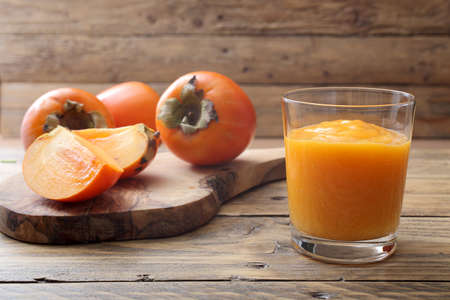 Persimmon fruit and smoothie on rustic table background