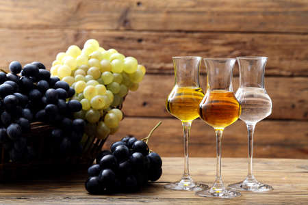 Glasses of grappa on rustic table background