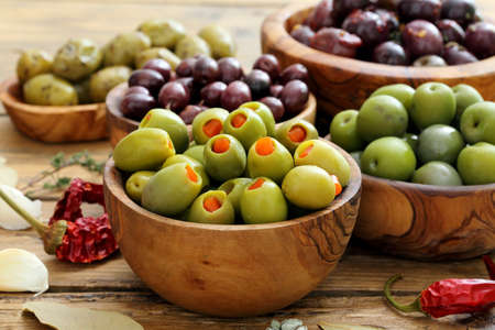 Assortment of olives in wooden bowl on kitchen table background