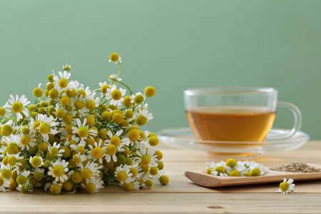 Chamomile tea and flowers on kitchen table background