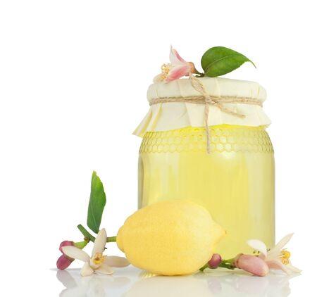 Honey, lemon  and lemon flower.  Isolated on a white background with reflection.