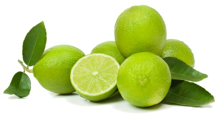 Fresh limes whole and half with green leaves. Isolated on white