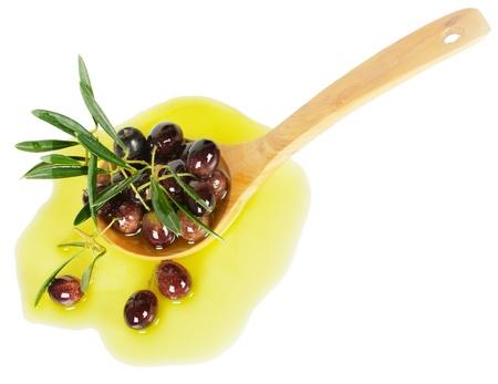 aceite de oliva: rama de olivo empapado en aceite de oliva en una cuchara de madera aislada en blanco