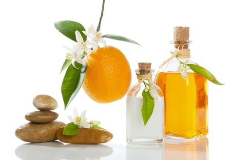 spa stilleven met oranje olie, room, bloesem en fruit op wit wordt geïsoleerd Stockfoto