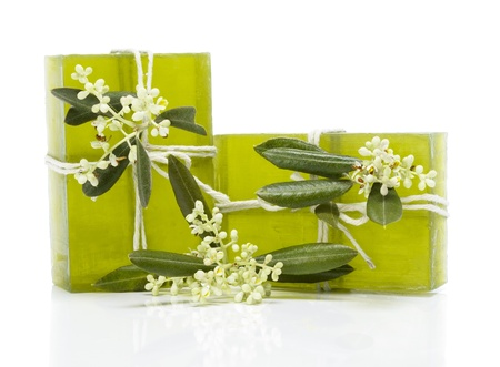 Two pieces of green soap with a sprig of  olive blossoms isolated on white background  photo