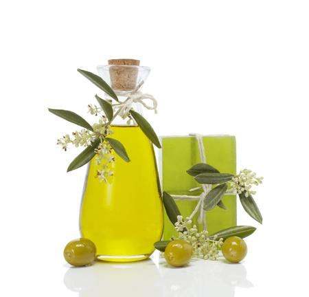 Olijfzeep met een takje van olijven bloesems, olie en olijven op een witte achtergrond
