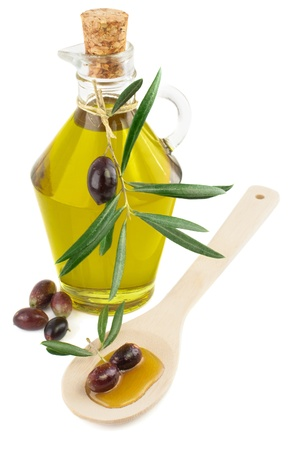 olive oil in a glass bottle and  olives with leaves on a wooden spoon  isolated on white background Banco de Imagens